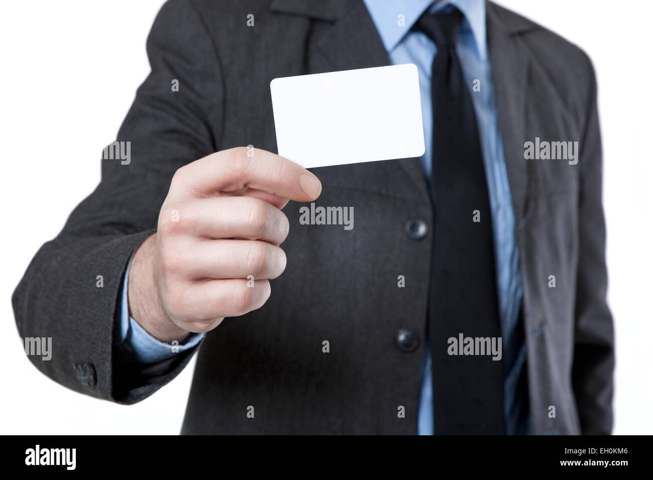 Man in suit with tie holds a white business card in hand, no face ...