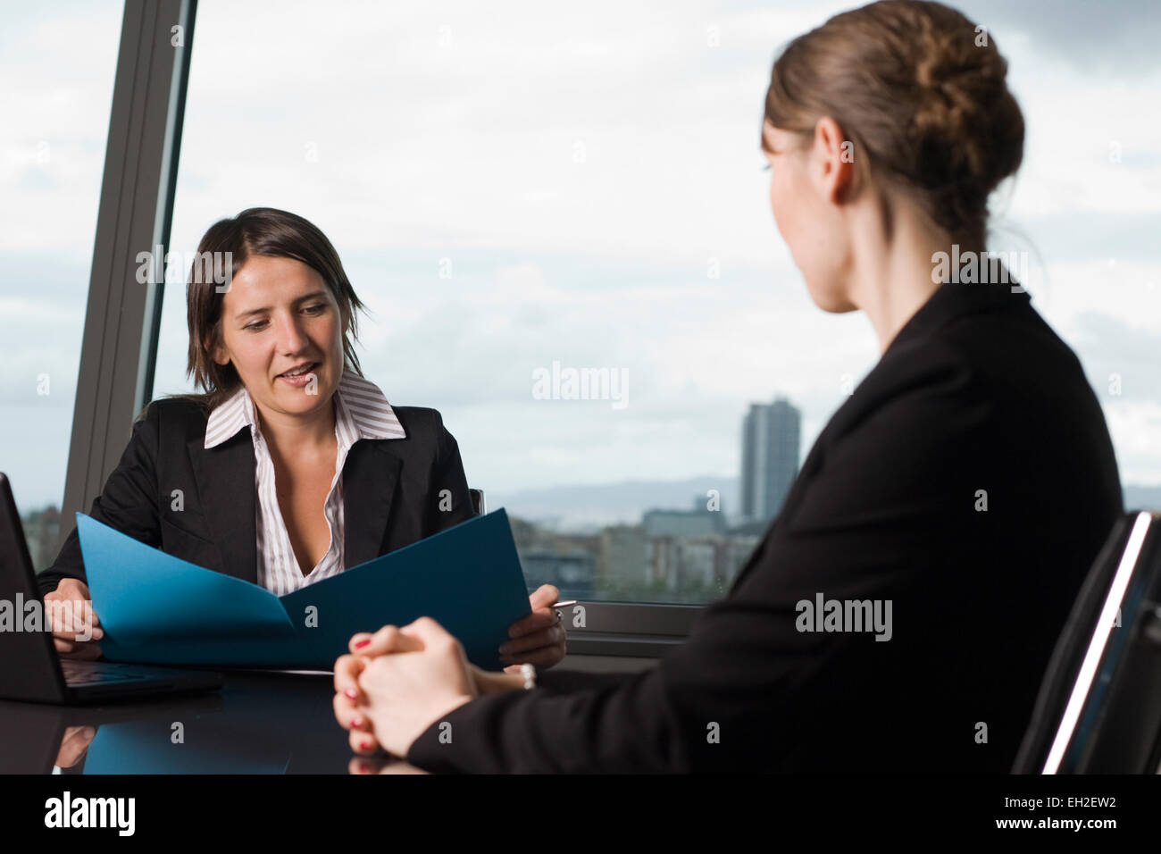two persons sitting at a table in office during job interview stock photo two persons sitting at a table in office during job interview