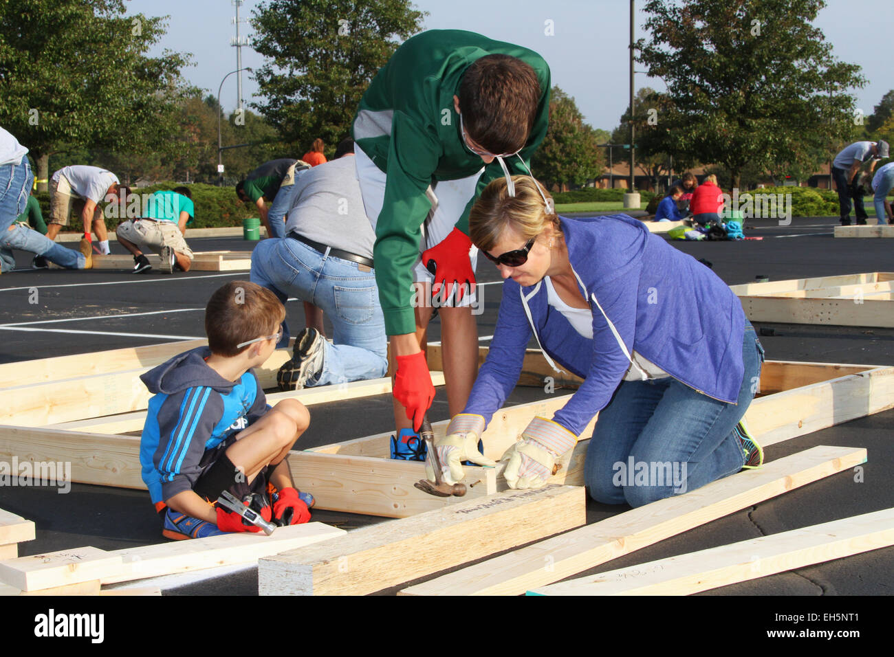 Mother and children. Volunteer people building a house ...