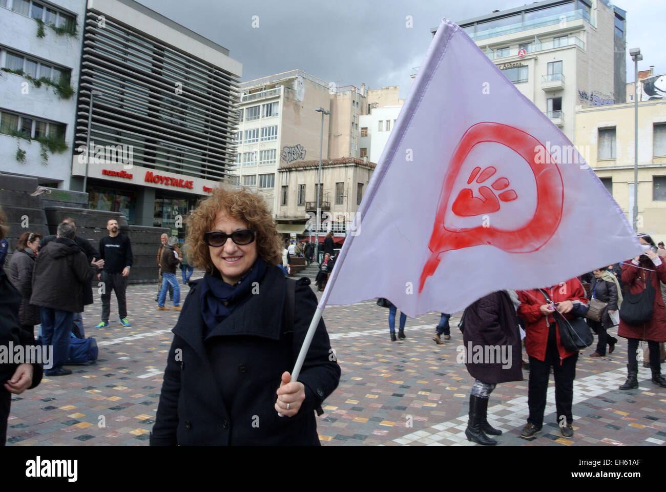 A demonstrator holds a flag with the symbol of feminism people in a demonstrator holds a flag with the symbol of feminism people in athens gathered in monastiraki square to commemorate iwd international womens day that buycottarizona Image collections