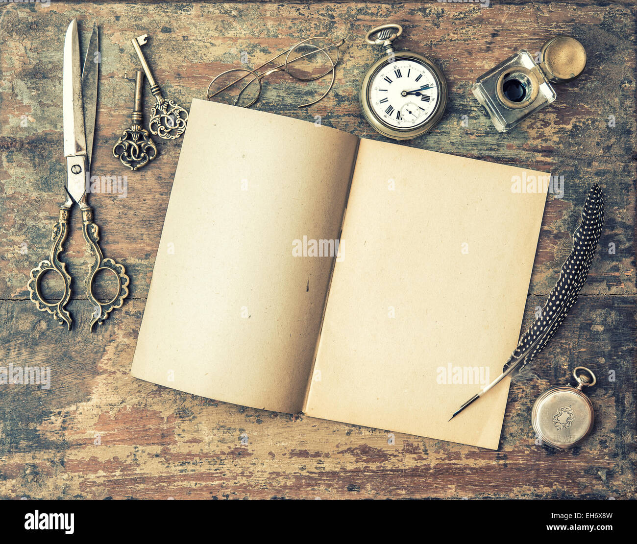 open journal book and vintage writing tools on wooden