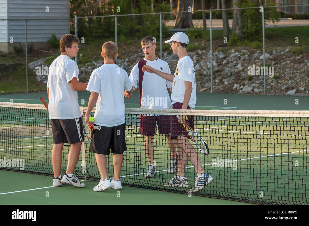 High school boys shaking hands after a tennis match in ...