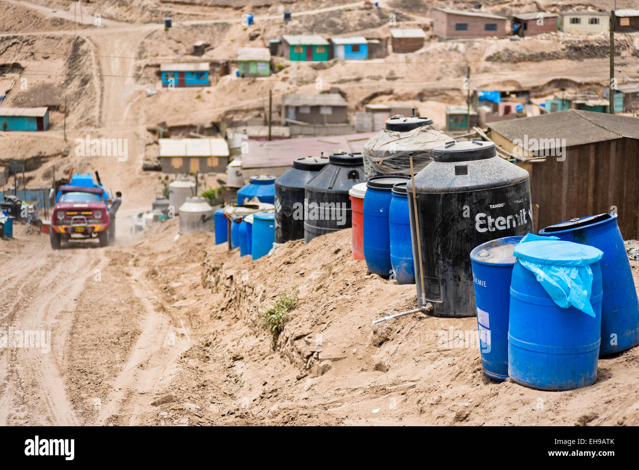 plastic barrels and water tanks used for water storage are seen along the sandy path on the dusty hillside in lima peru - Water Storage Barrels