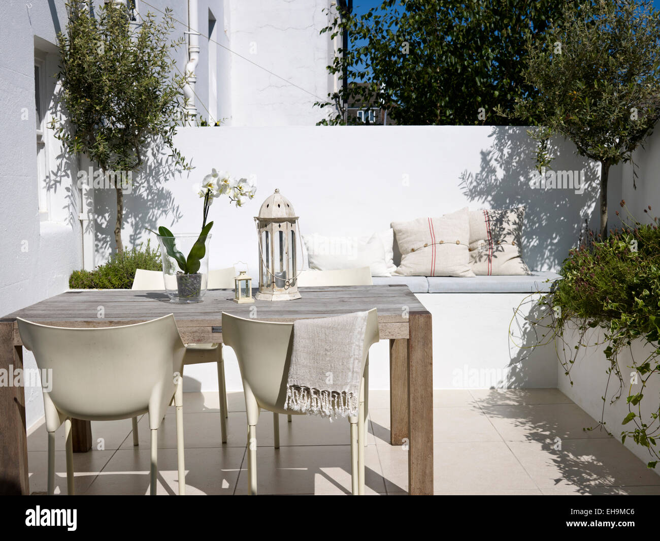 paved backyard with plants table and seating residential house