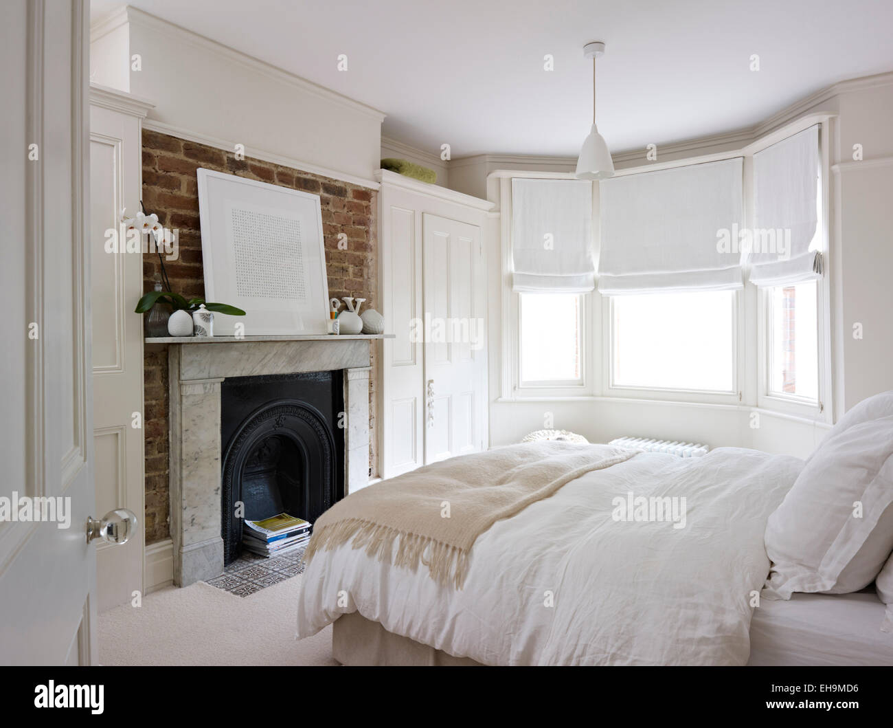 bedroom with bed fireplace and bay window with roman blinds stock