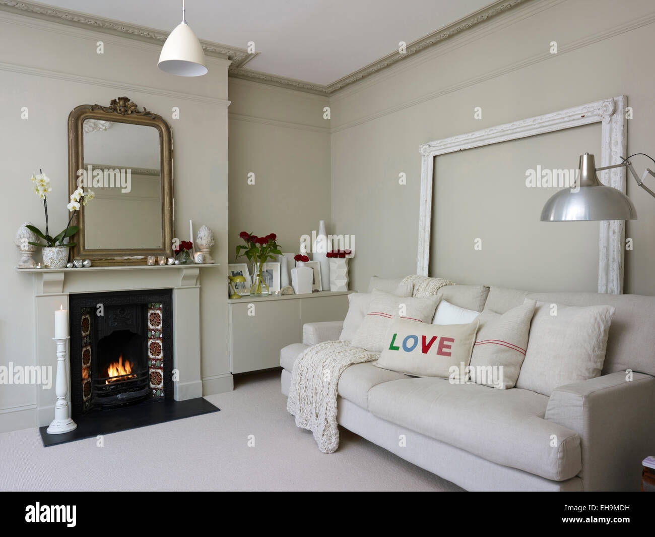 white sofa in front of open fire in white sitting room