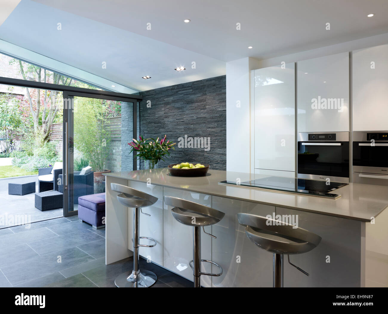 breakfast bar with stools in open plan kitchen and living area in
