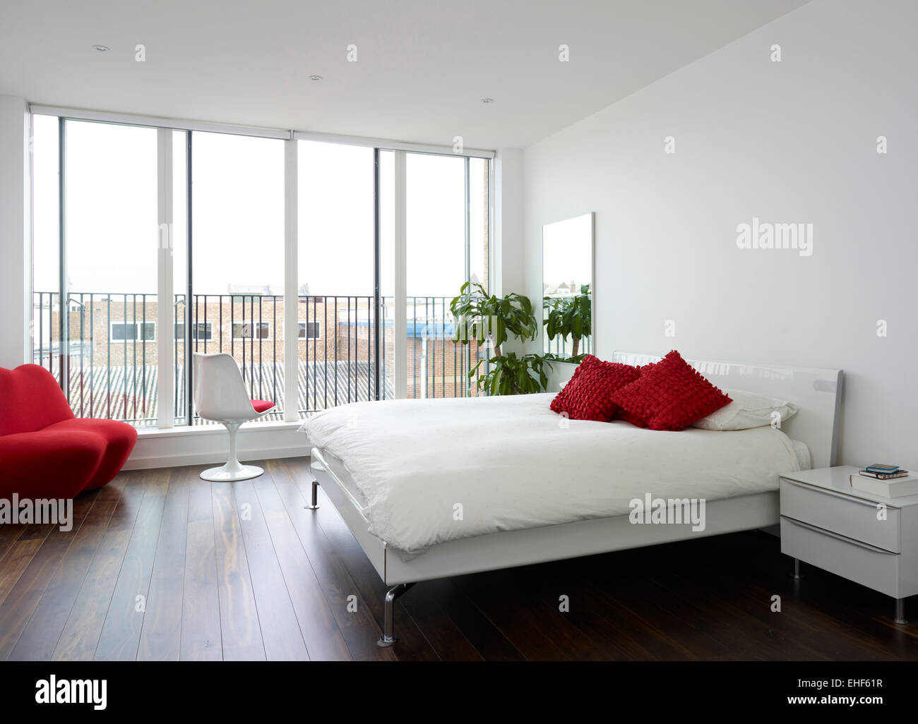 Modern bedroom with dark wooden flooring and red chair double bed and  balcony in The GapRed Chair For Bedroom   VesmaEducation com. Red Accent Chair For Bedroom. Home Design Ideas