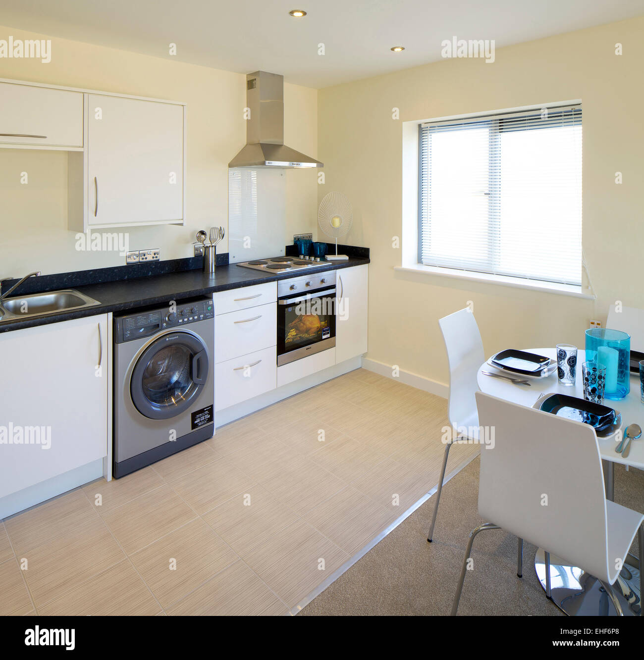 Modern kitchen with white units and breakfast table and chairs in ...