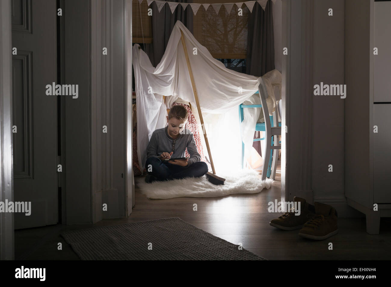 Boy sitting in self-made tent at home in the evening using digital tablet & Boy sitting in self-made tent at home in the evening using digital ...