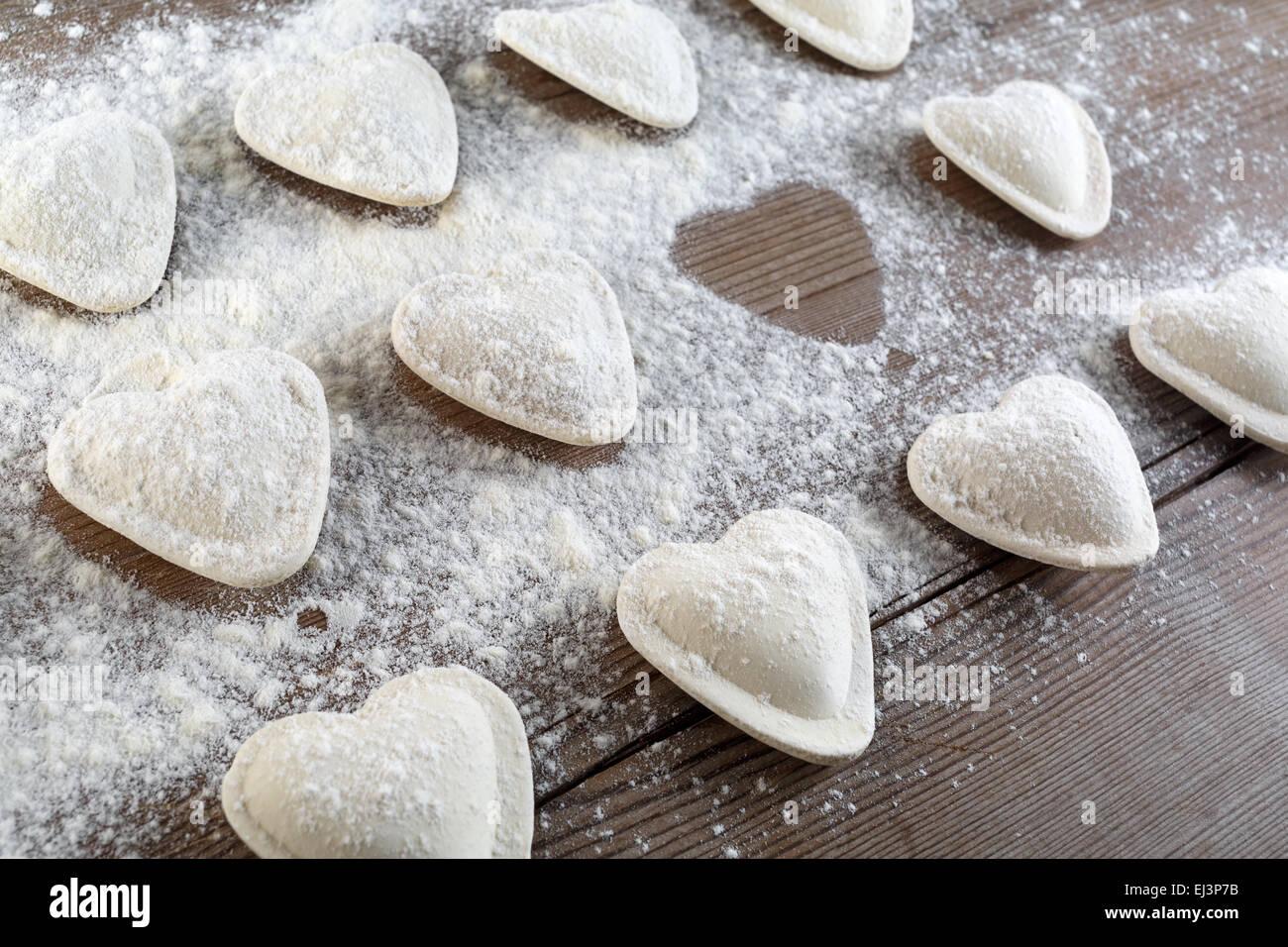 Cooking ravioli. Raw dumplings in the form of hearts sprinkled flour ...