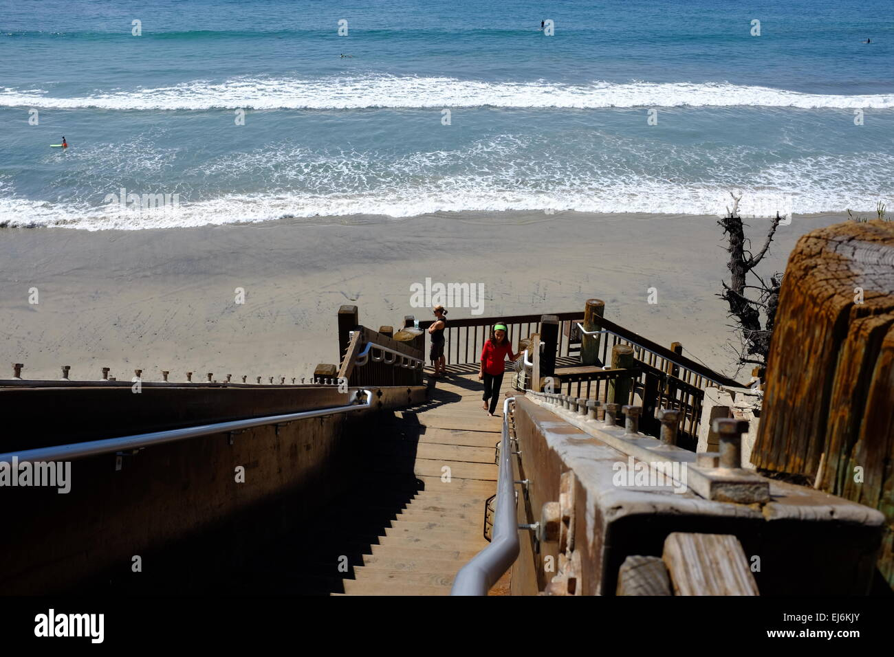 Grandview Beach Access In Encinitas, CA, Woman Walking Up The Stairs From  The Beach, Surf In The Background