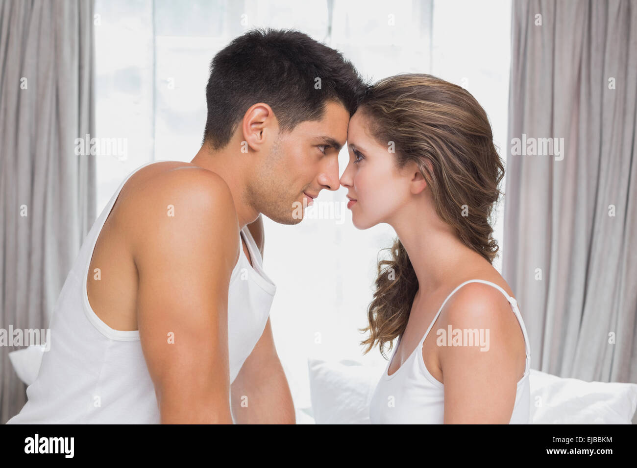 Romantic couple sitting in bed at home. Romantic couple sitting in bed at home Stock Photo  Royalty Free