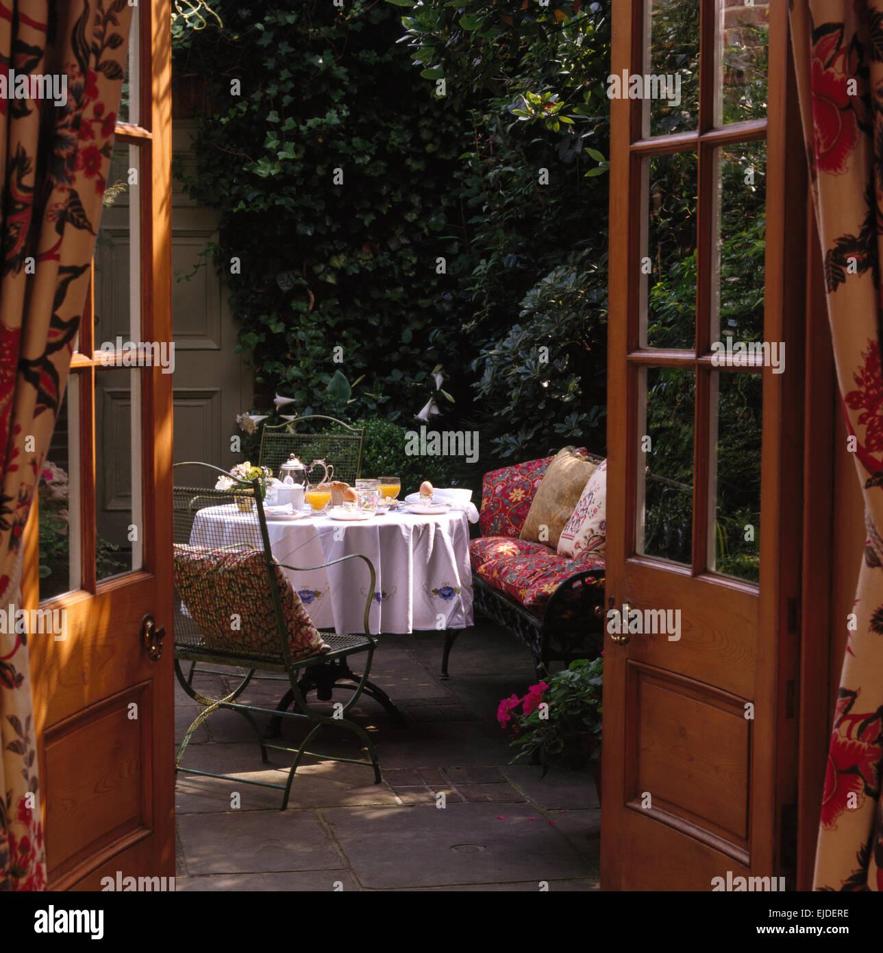 View through french doors of terrace with table set for breakfast view through french doors of terrace with table set for breakfast in small town garden rubansaba