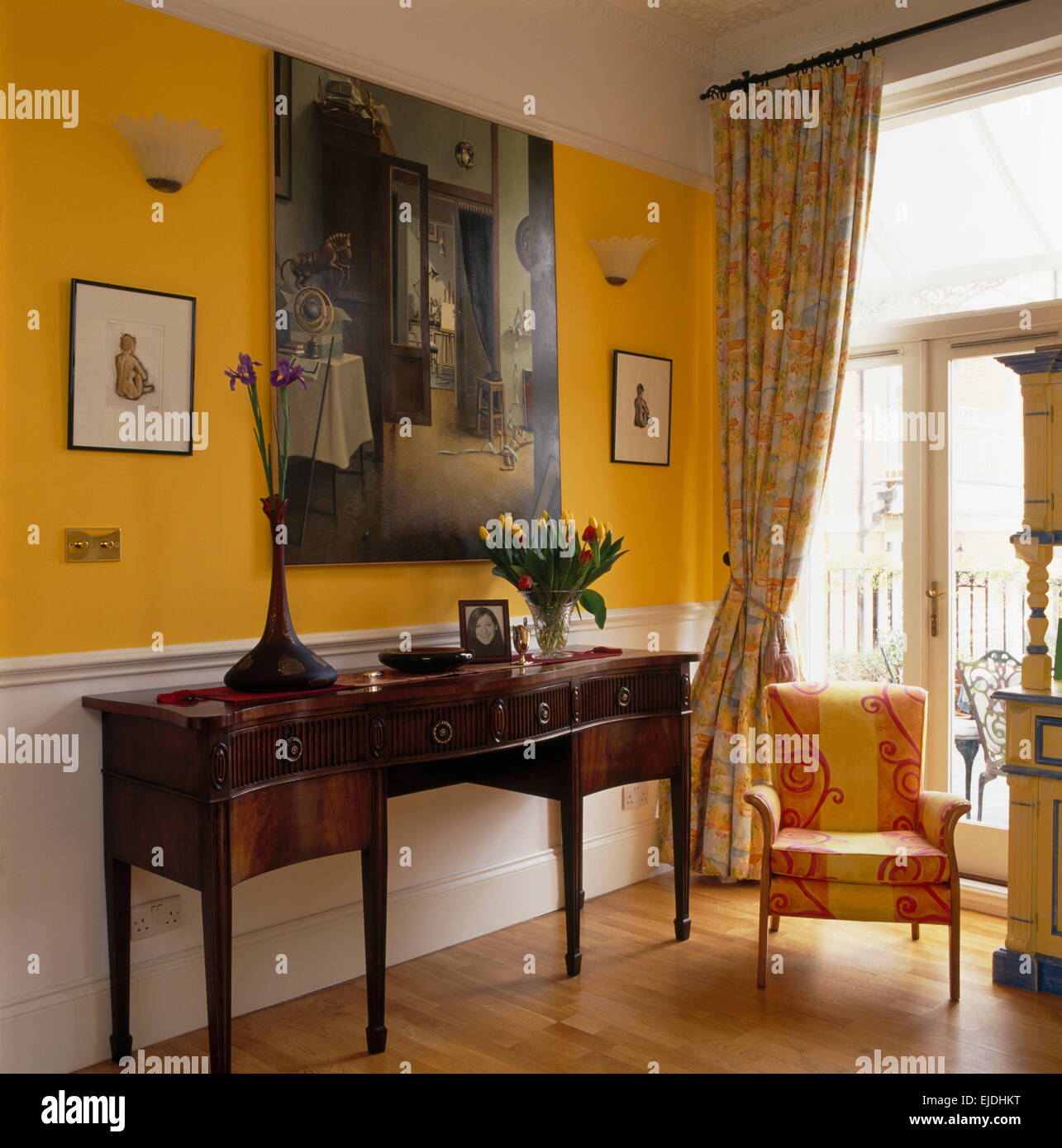 Large Painting Above Antique Console Table In Bright Yellow Hall With Yellow+pink  Upholstered Chair And Wooden Flooring