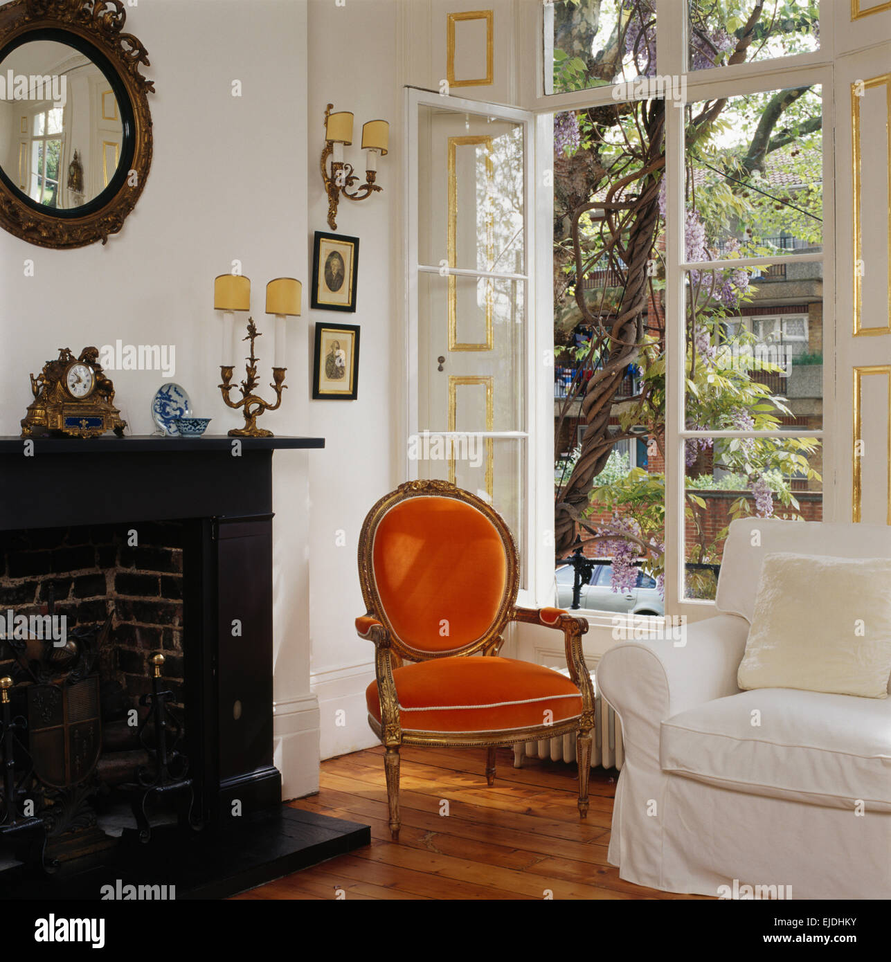 Orange velvet French style chair in front of open window in ...