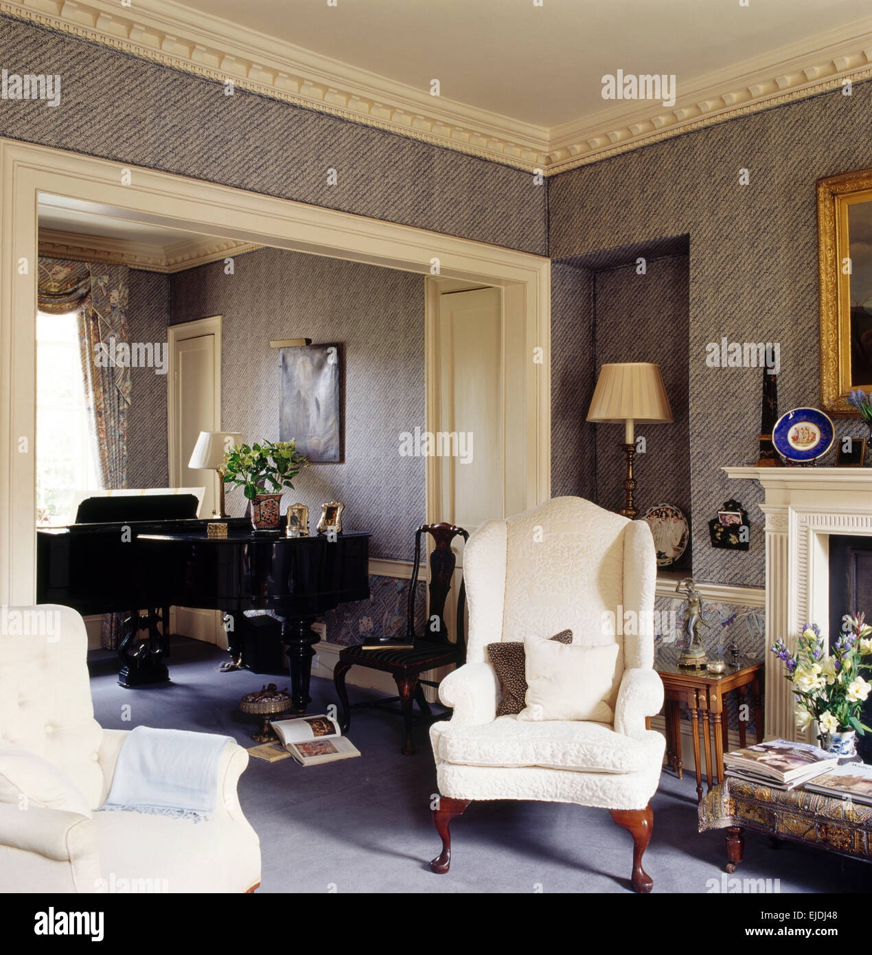 Cream wing chairs in townhouse living room with gray wallpaper and ...