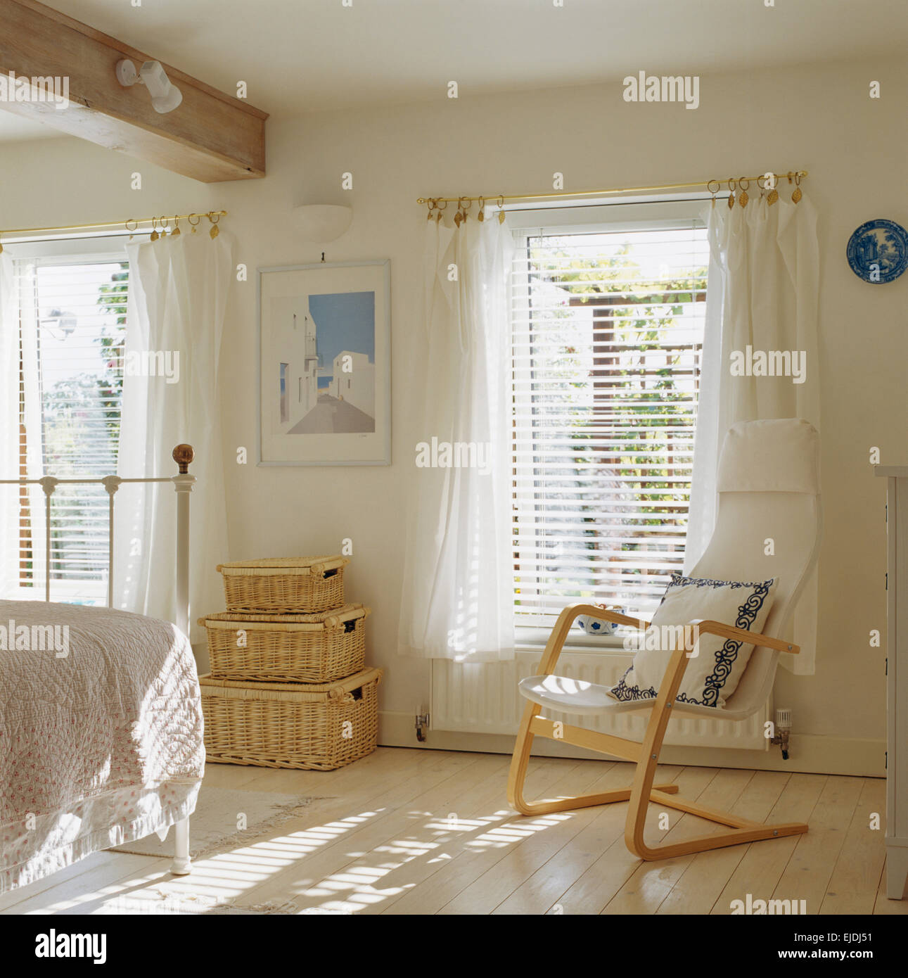 Scandinavian style wooden chair and wicker chests in white bedroom