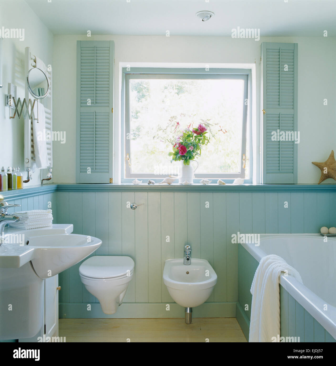 Pale Blue Shutters On Window Above Toilet And Bidet In Country Bathroom With Painted Tongue Groove Paneling