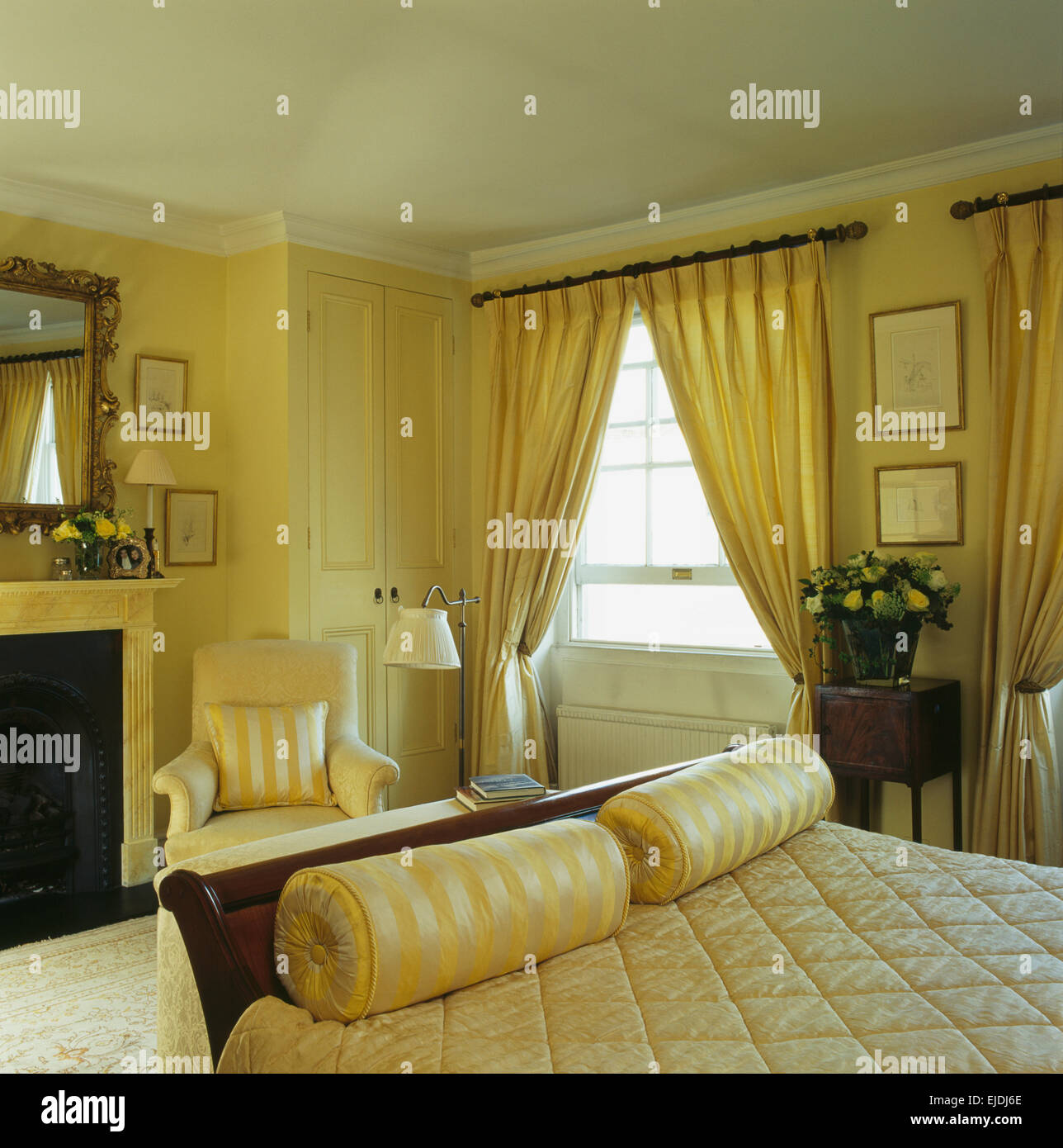 Yellow Silk Bolster Cushions At The Foot Of Bed In Townhouse Bedroom With