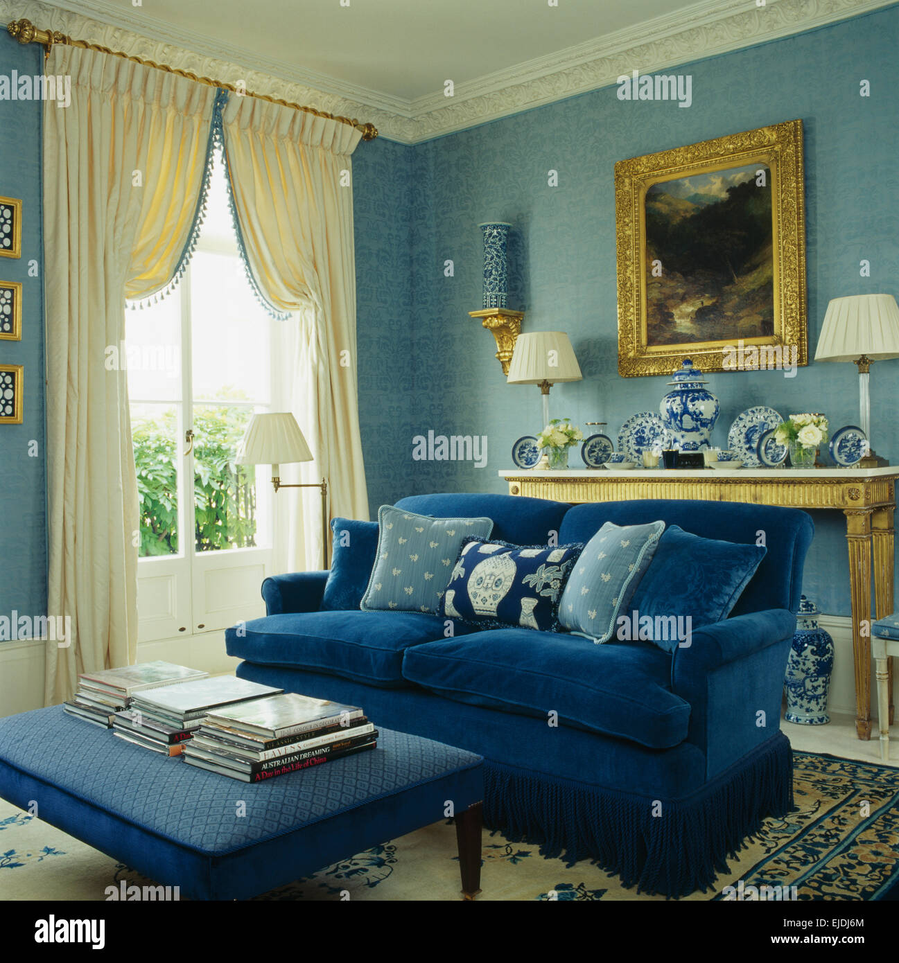 Stock Photo   Upholstered Stool And Deep Blue Sofa With Toning Blue  Cushions In Blue Living Room With Cream Drapes On French Windows