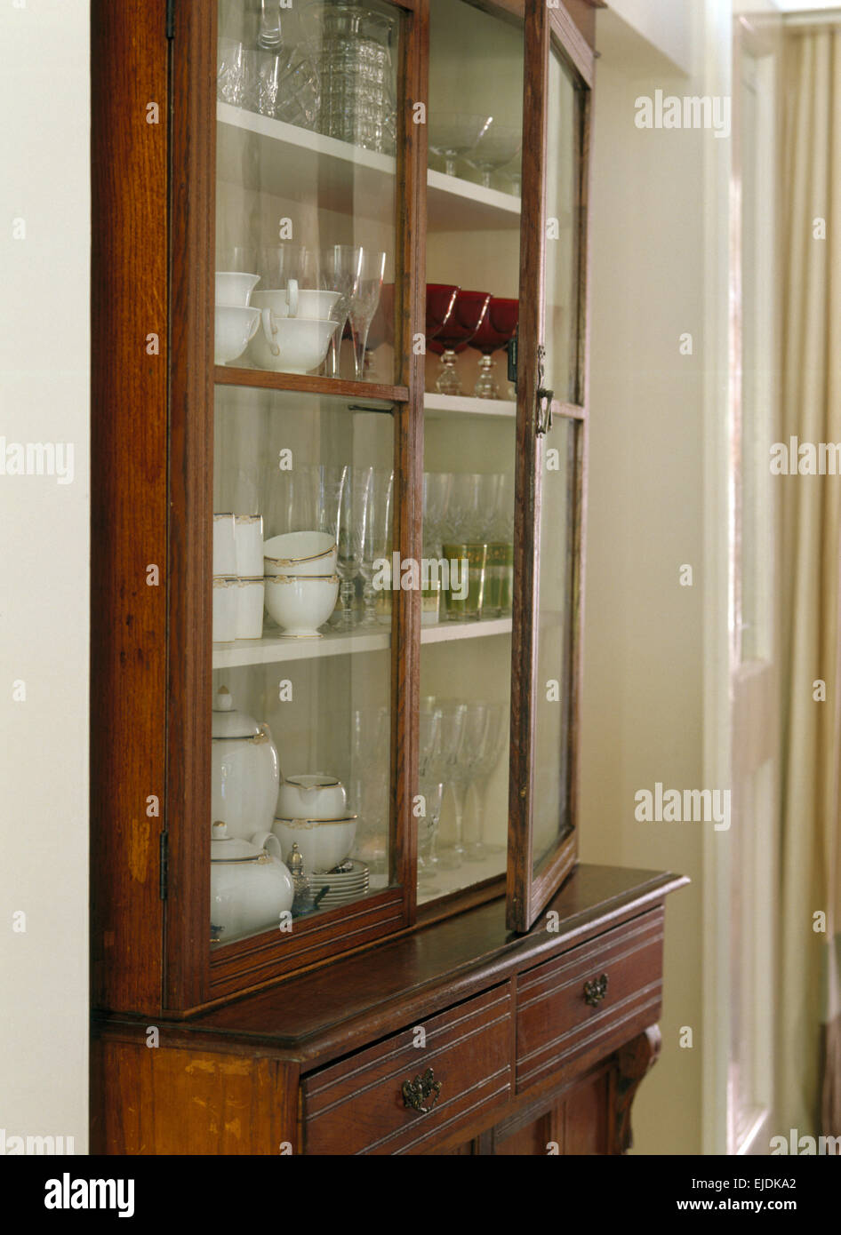 Close Up Of Antique Glass Front Dresser With Glassware And White China