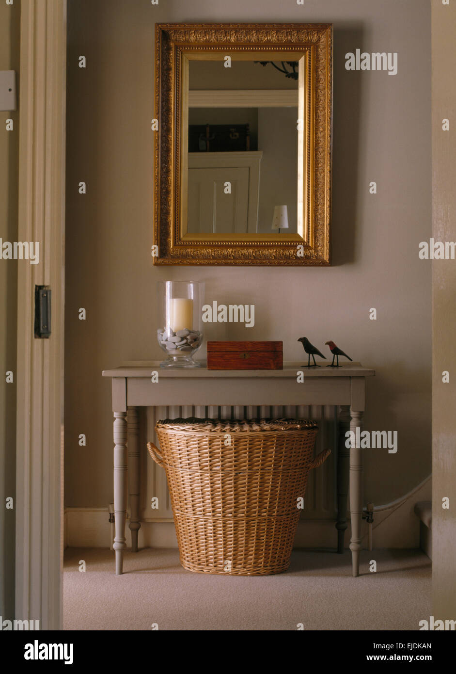 Rectangular Gilt Mirror Above Pale Gray Console Table And Large Wicker  Basket In Townhouse Hall