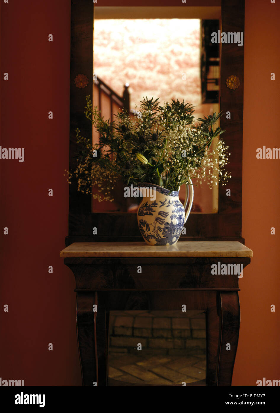 Mirror on wall above table with vase of summer flowers in country mirror on wall above table with vase of summer flowers in country hall reviewsmspy