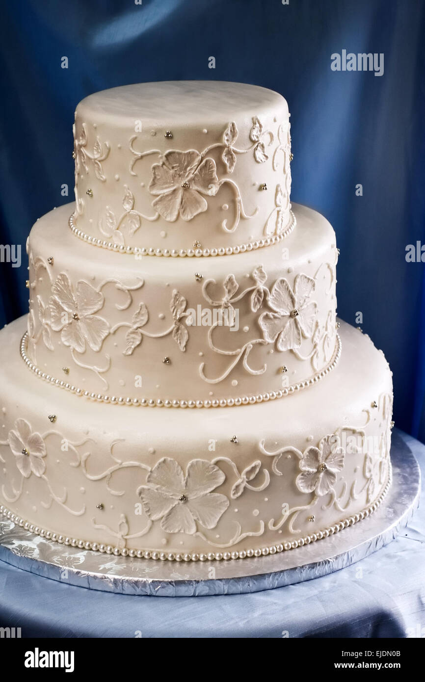 Three tiered wedding cake covered in ivory fondant with piped ...