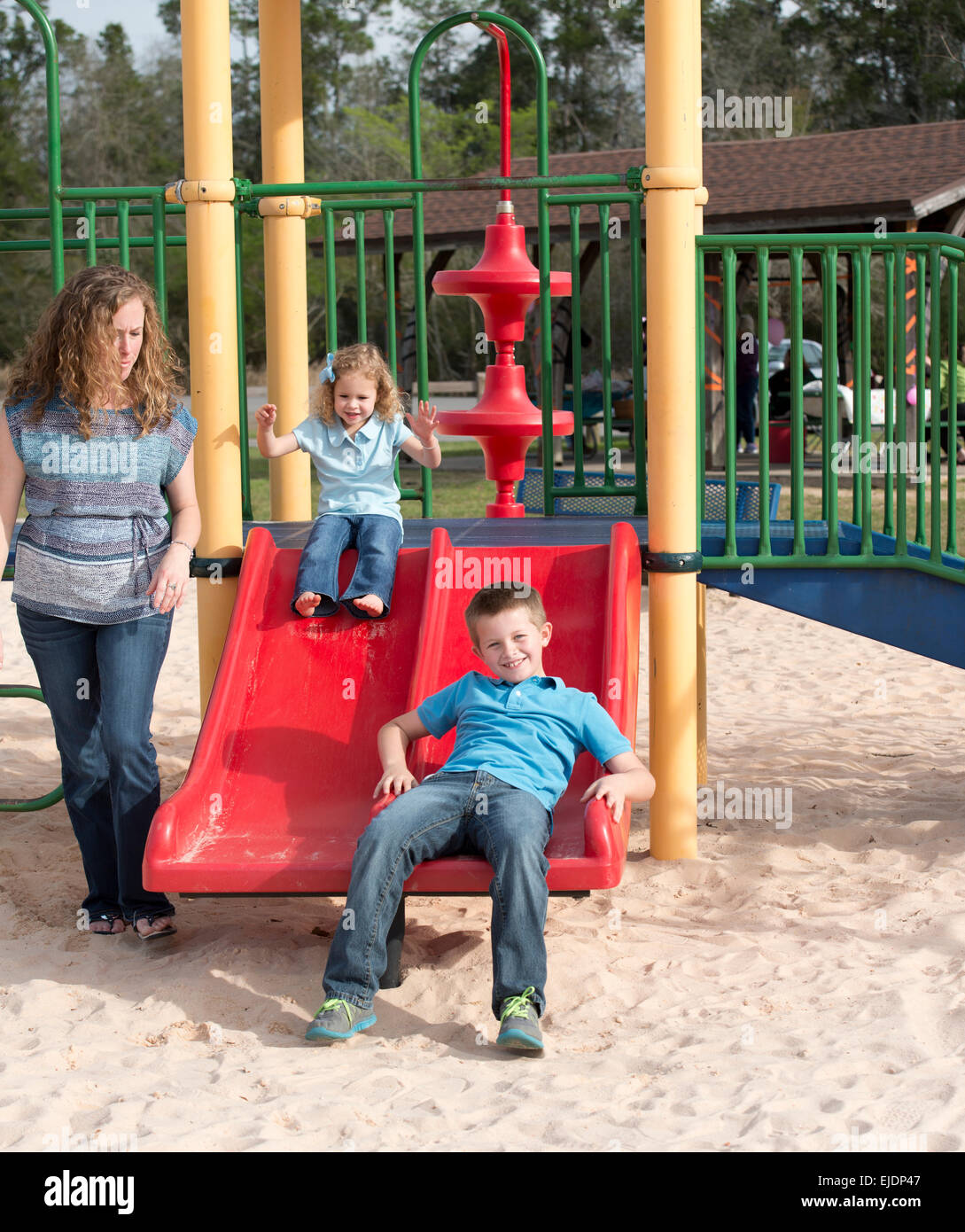 Young Boy And Girl Go Down Slide On Park Playground While Mom Looks