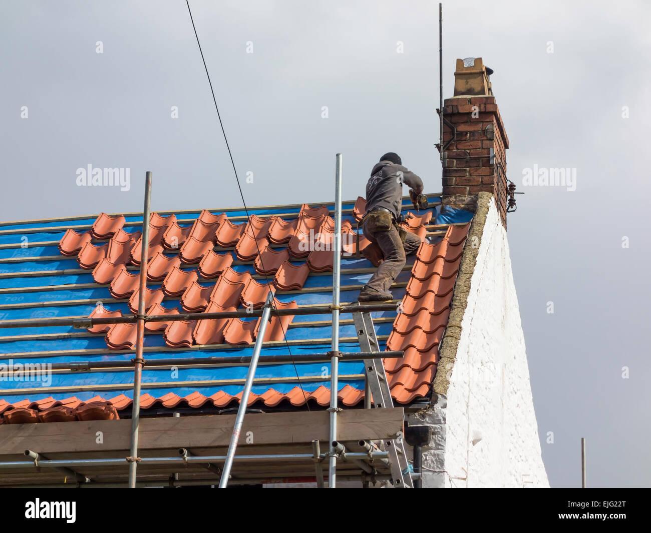 A Tiler Man Replacing Roof Tiles On A House