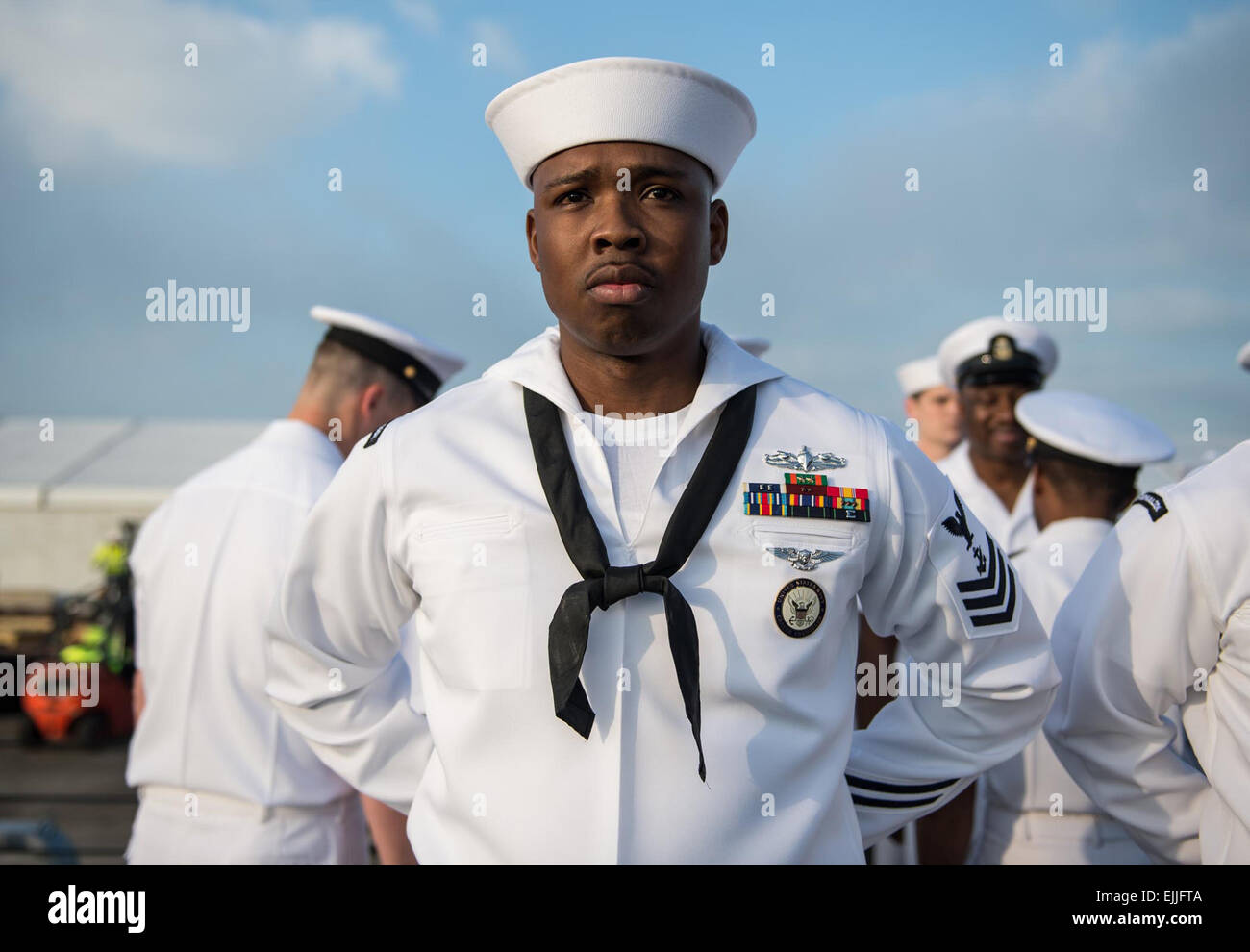 A US Navy sailor stands at parade rest during a uniform inspection ...