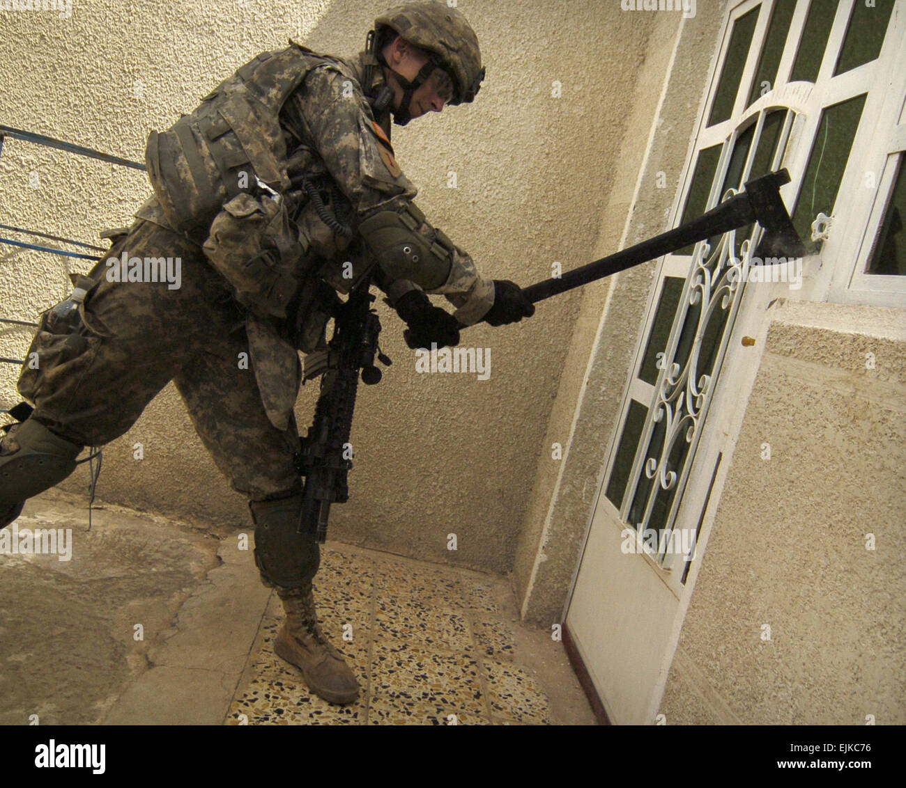 U.S. Army Sgt. David Bauer attempts to breach a door during a house-to-house search for illegal weapons explosives and high value targets in the Sadiyah ... & U.S. Army Sgt. David Bauer attempts to breach a door during a ...