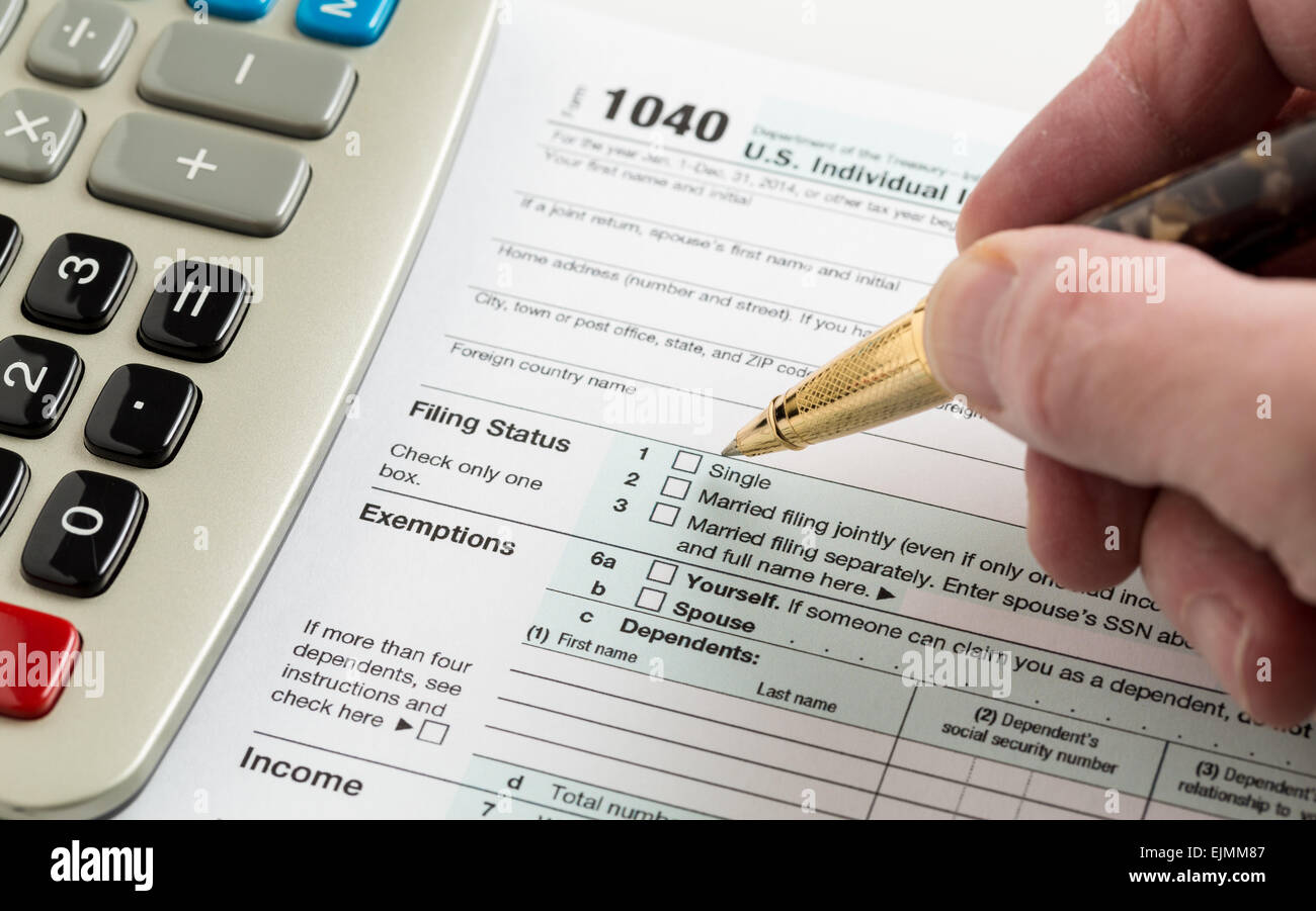 Male caucasian hand holding pen above usa tax form 1040 for year male caucasian hand holding pen above usa tax form 1040 for year 2014 and calculator illustrating completion of tax forms for t falaconquin