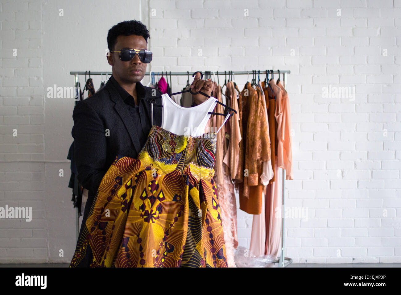 South african fashion designer david tlale poses with one for Designer david