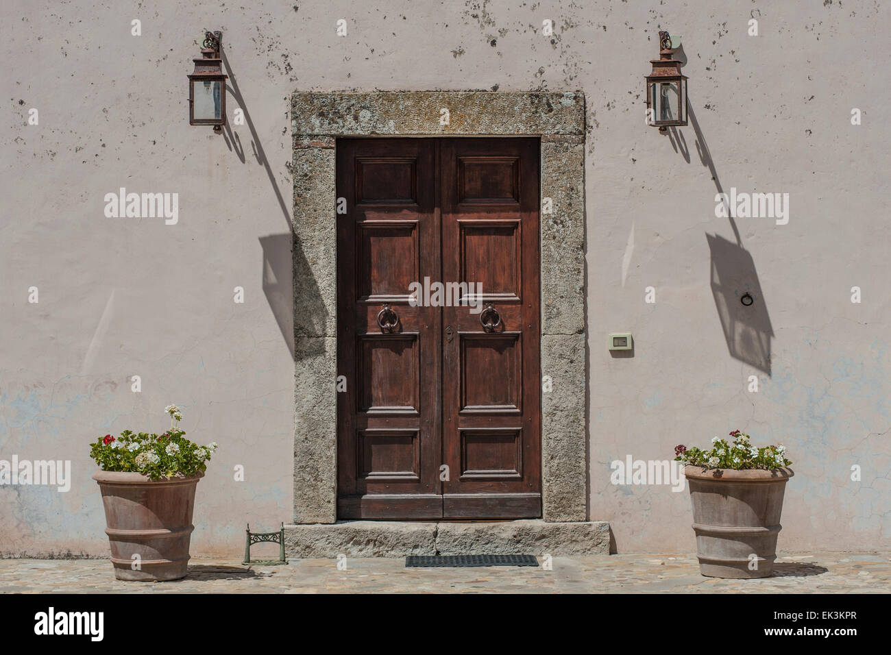 A Big Heavy Front Door On An Italian House With The Shadow Of Lights And  Pot Planters With Flowers