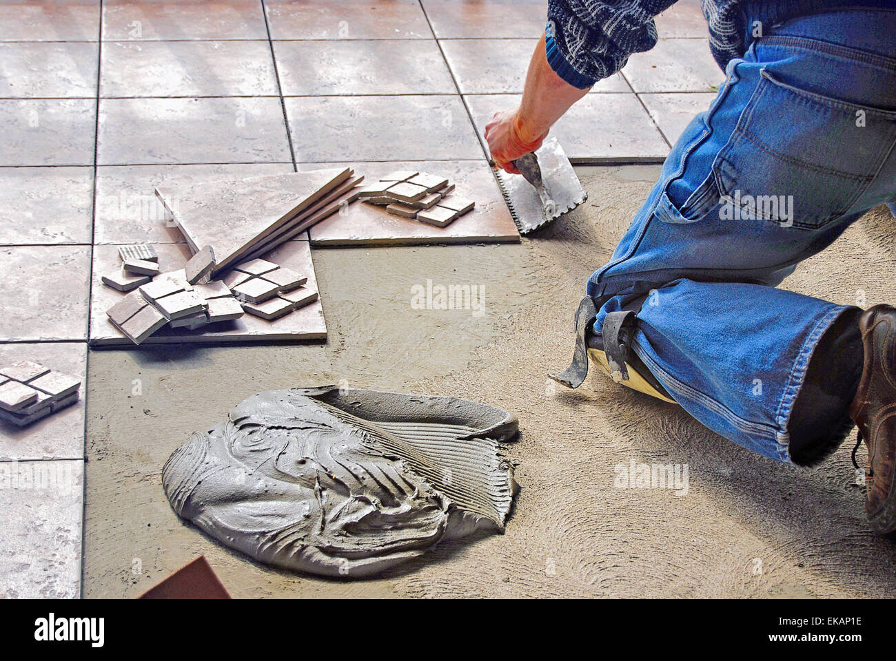 Tile layer on his knees using a trowel to install floor tile stock tile layer on his knees using a trowel to install floor tile dailygadgetfo Gallery