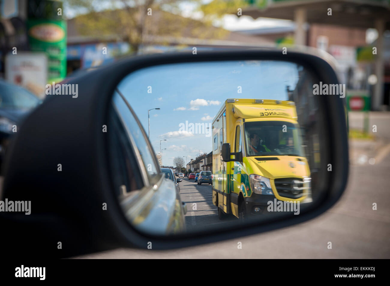 an racing ambulance with flashing lights overtakes a car which sees