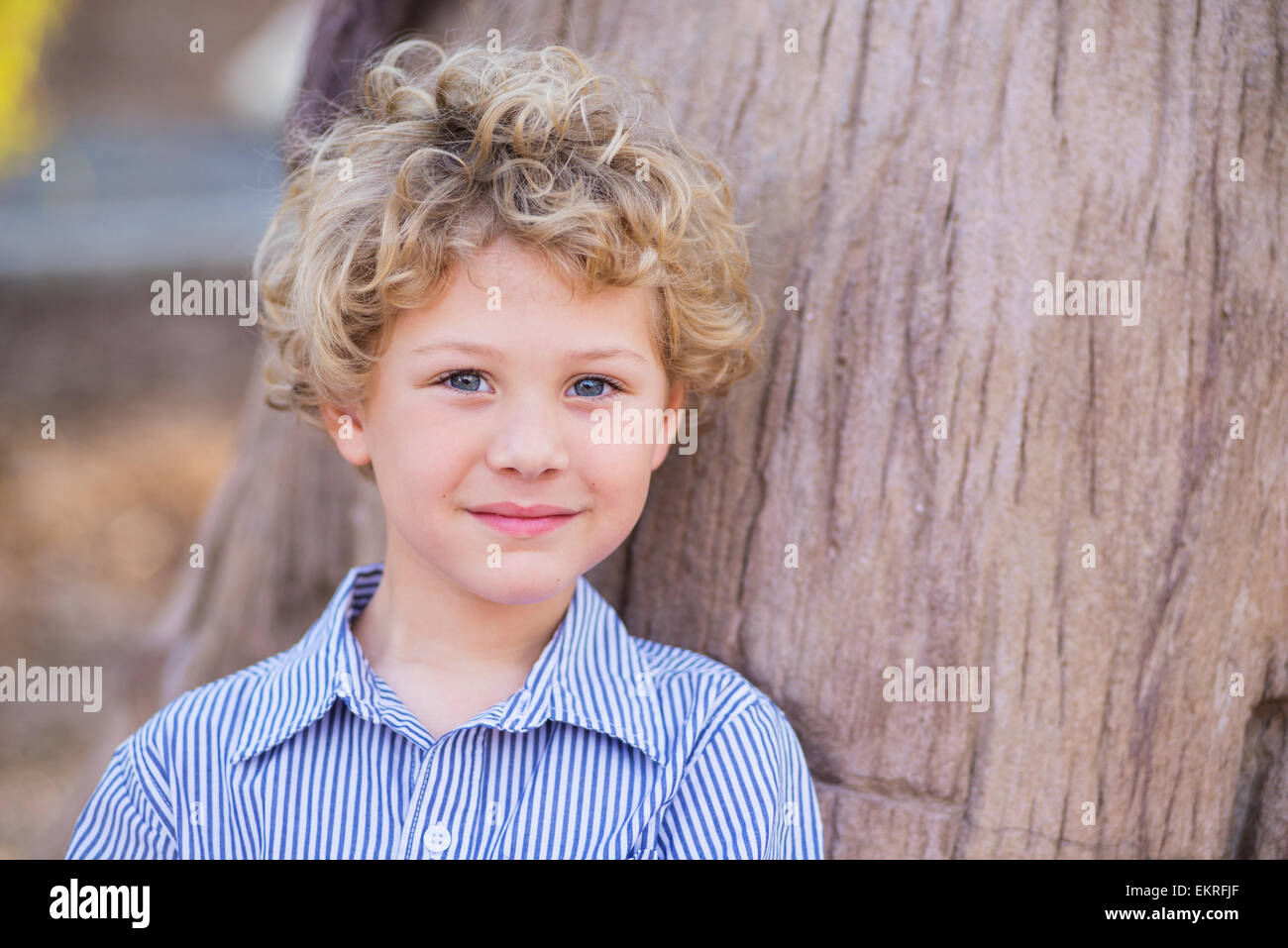 Portrait Of A Young Boy With Blond Curly Hair And Blue Eyes Stock