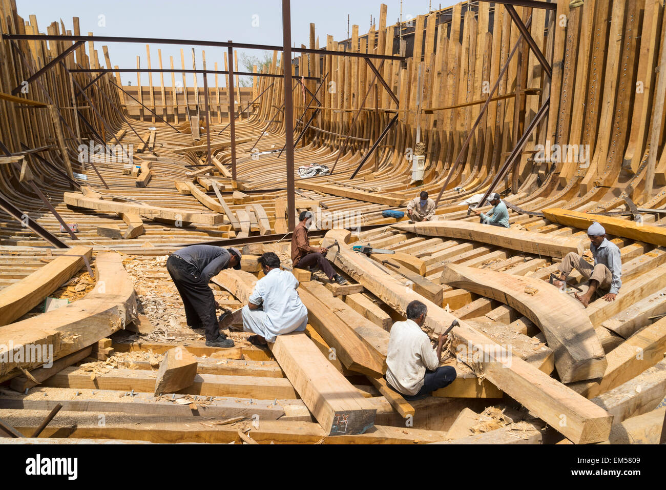Craftsmen Building A Traditional Wooden Dhow Cargo Ship In Shipyard Beside The Creek River Dubai United Arab Emirates