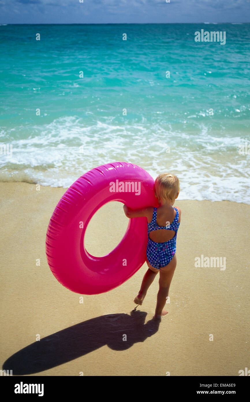Little Girl Runs To Water With Beach Tube B