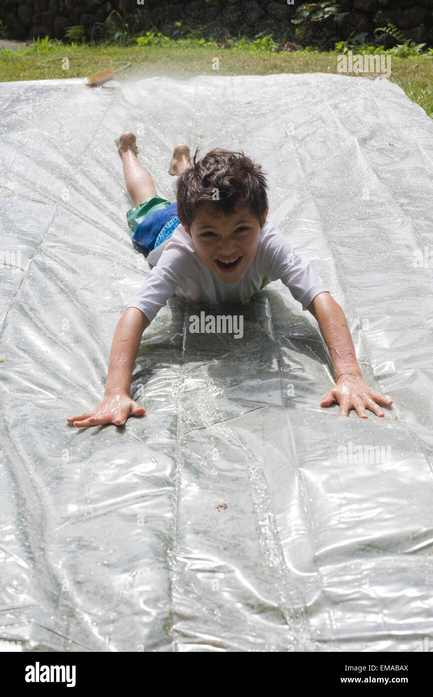 seven year old boy plays on a homemade slip and slide in his