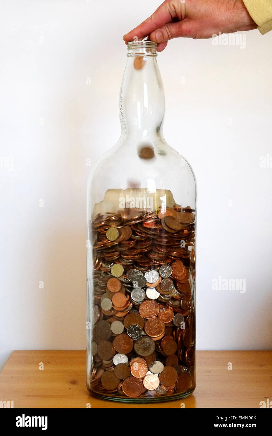 Man Dropping Coins Into A Large Glass Bottle Nearly Full