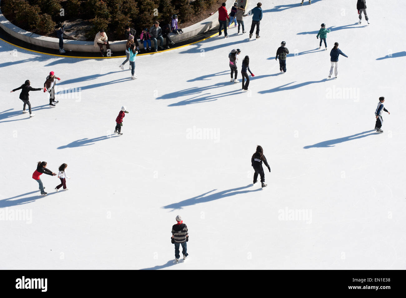 Aerial view of people skating in community rink during ...