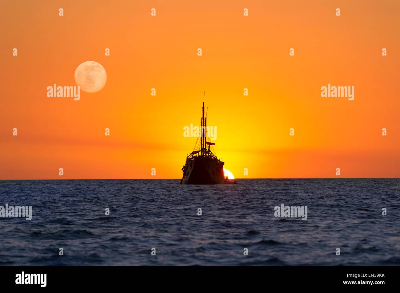Old Wooden Ship Sits At Sea As The Sun Sets And Moon Rises Like A Fantasy