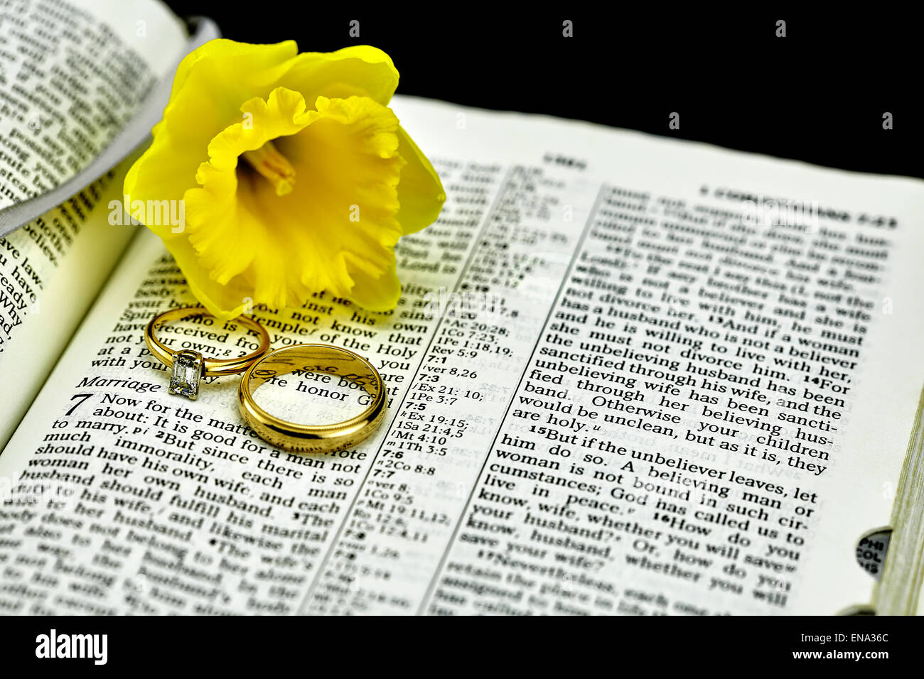open bible book with selective focus on marriage and diamond and gold wedding rings and yellow