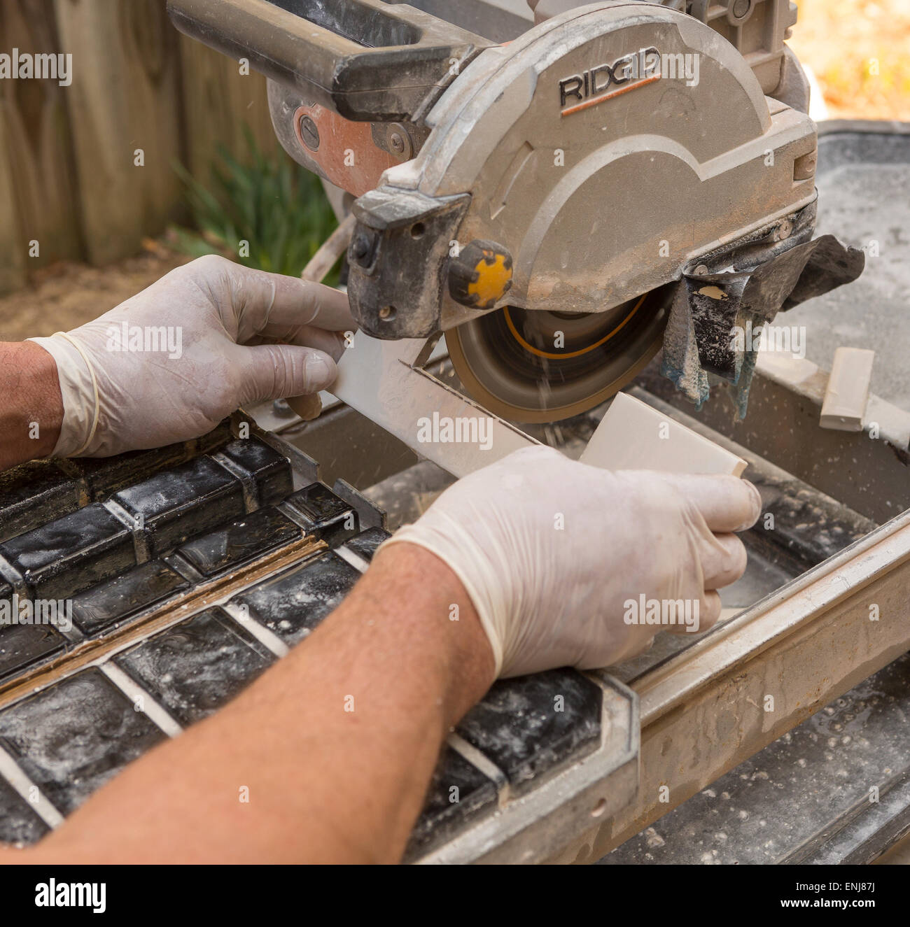 Arlington virginia usa worker wearing latex gloves cuts arlington virginia usa worker wearing latex gloves cuts ceramic tiles with a wet tile saw dailygadgetfo Gallery
