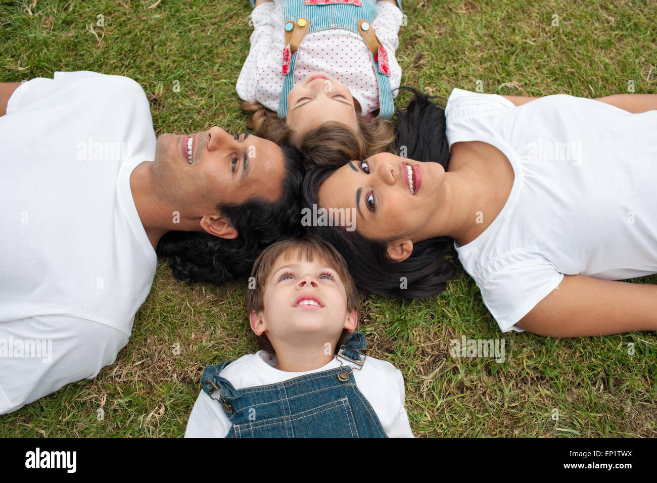 Jolly Parents And Their Children Lying On The Grass Stock