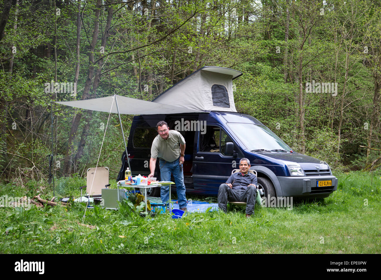 Two men cooking and camping with their Ford Transit Connect camper