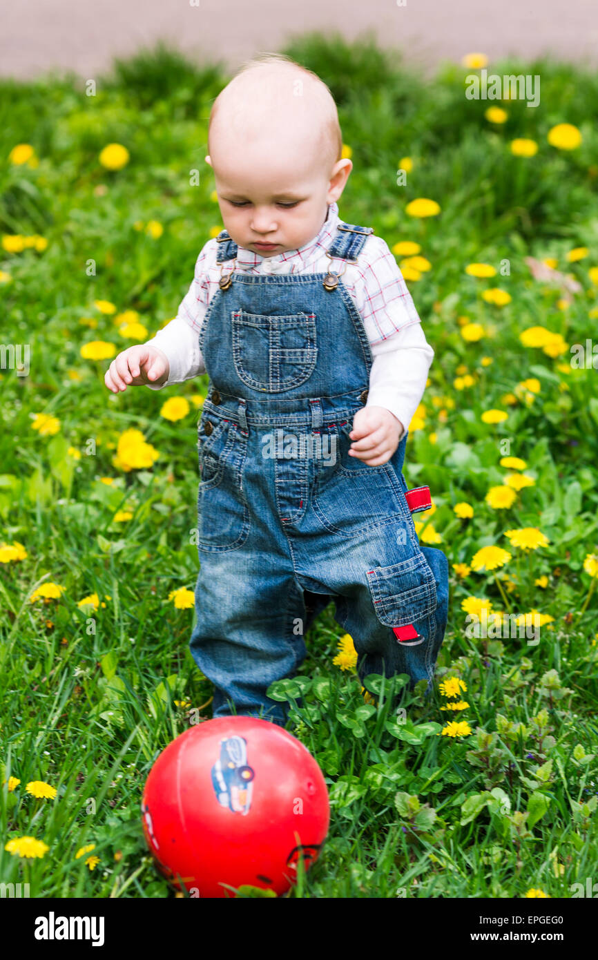Cute baby boy with a ball on dandelions lawn summertime Stock Photo ...